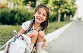 Outdoors Portrait Of Happy Little Girl Preschooler Smiling Broadly And Sitting On Doorstep With Back poster