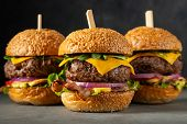 A Set Of Homemade Delicious Burgers Of Beef, Bacon, Cheese, Lettuce And Tomatoes On A Dark Concrete  poster
