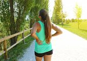 Back Pain. Athletic Running Woman With Back Injury In Sportswear Rubbing Touching Lower Back Muscles poster