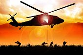 image of attack helicopter  - Helicopter is dropping the troops on grass field - JPG