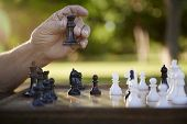 picture of time-piece  - Active retired persons hand of old man holding chess piece in park - JPG