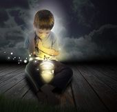 stock photo of fireflies  - A boy is looking at a glowing bug firefly coming out of a jar with a butterfly at night for an imagination or hobby concept - JPG