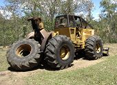 stock photo of skidder  - Logging skidder heavy equipment bulldozer used to snig cut logs - JPG