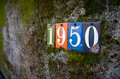 image of nineteen fifties  - The numbers 1950 are attached to an old wall covered in moss and dirt - JPG