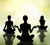 stock photo of pranayama  - silhouettes of three women practicing yoga lotus pose - JPG