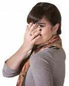 image of coy  - Coy Hispanic female hiding part of face with hand - JPG