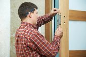 image of carpenter  - Male handyman carpenter at interior wood door lock installation - JPG