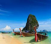 Постер, плакат: Праздник отпуск концепции фон длинный хвост лодки на тропическом пляже с известняковые скалы Краби T
