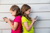 Twin sister girls playing with tablet pc happy on white wall leaning on her back
