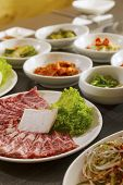 picture of kimchi  - A vertical shot of beef with korean side dishes.