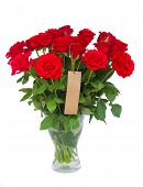 bouquet  of scarlet roses in vase with tag