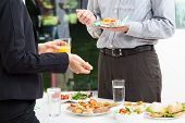 stock photo of buffet lunch  - Business colleagues talks during a lunch outdoor  - JPG