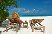 Woman at beautiful beach with chaise-lounges
