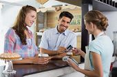 stock photo of debit card  - Side view of a couple paying bill at coffee shop using card bill - JPG