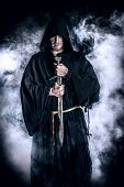 image of wander  - Portrait of a courageous warrior wanderer in a black cloak and sword in hand - JPG