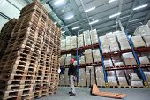 pic of hand truck  - stack of wooden pallets in storehouse  - JPG