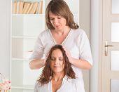 stock photo of reiki  - Professional Reiki healer doing reiki treatment to young woman - JPG