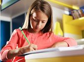 picture of homework  - child concentrating on homework in bedroom - JPG