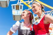 picture of national costume  - Friends visiting together Bavarian fair in national costume or Dirndl in front of ferris wheel - JPG