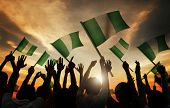 stock photo of nigeria  - Silhouettes of People Holding Flag of Nigeria - JPG