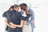 picture of huddle  - Business team all huddled together in a circle - JPG