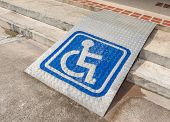 picture of disability  - Ramped access using wheelchair ramp with information sign on floor background for disabled people - JPG