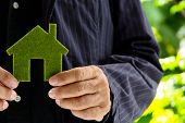 image of economizer  - senior man holding green icon house concept - JPG