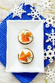 picture of canapes  - canape with salmon and cream cheese with dill for Christmas on a light woody background - JPG