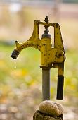 stock photo of spigot  - Dripping Water Spigot Pump on farm with rock and water drop - JPG