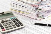 stock photo of financial audit  - calculator and invoices on financial summary report - JPG