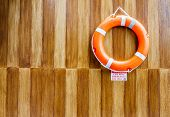 Постер, плакат: The Orange Life Buoy With The Wood Wall Background For Safety And Rescue