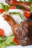 image of roast duck  - roasted duck leg with rice and basil on lettuce on a white plate macro vertical - JPG