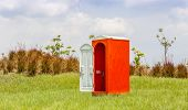 pic of hillbilly  - Standalone of red water closet or toilet in the green meadow with clear blue sky - JPG