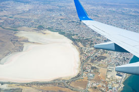 stock photo of larnaca  - The aircraft decreases altitude over the salt lake of Larnaca to make a landing in Larnaca International Airport Cyprus - JPG
