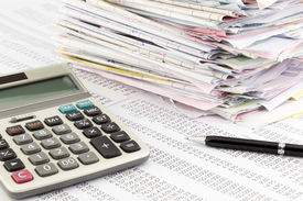 pic of summary  - calculator and invoices on financial summary report - JPG