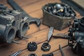 picture of carburetor  - Carburetors for a car engine with tools on wooden table - JPG