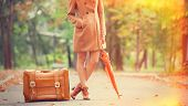 pic of gril  - Gril in coat with umbrella and suitcase in the park - JPG