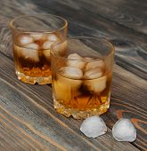 stock photo of scotch  - Glasses with Scotch and ice on old wooden background - JPG