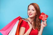 stock photo of redhead  - Redhead girl with shopping bags on blue background - JPG