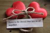 picture of tied  - two silky love hearts next to a loving quote and a tied knot on a wooden surface - JPG