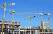 image of framing a building  - Crane and building construction site against blue sky - JPG