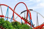 stock photo of breathtaking  - Roller Coaster in funny amusement  park in summer day - JPG