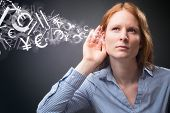 pic of hearing  - A young businesswoman listens to stock or financial market information  - JPG
