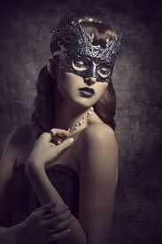 pic of venice carnival  - Gorgeous mysterious female in carnival silver mask with brown long hair and dark make up wearing black dress - JPG