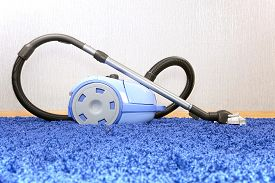 stock photo of laminate  - The metal pipe of vacuum cleaner in action  - JPG