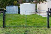 stock photo of chicken-wire  - Single galvanzed farm gate with rust chain locking it closed - JPG