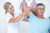 stock photo of stretch  - Doctor stretching a man arm in medical office - JPG