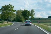 pic of speeding car  - Small car on country road with left turn and speed limit sign - JPG