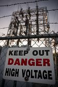 stock photo of chain link fence  - A sign reading Keep Out Danger High Voltage affixed to a chain - JPG