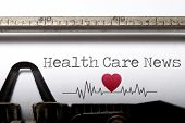 stock photo of beats  - Health care news printed on an old typewriter with heart beat pulse sketch - JPG